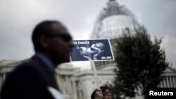 "FILE - A woman holds a sign showing a baby as she attends a ""Women Betrayed Rally to Defund Planned Parenthood"" at Capitol Hill in Washington, July 28, 2015."
