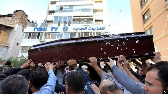 Mourners carry the coffin of Lebanese television cameraman Ali Shaaban, of Al-Jadeed TV who was shot dead on the Lebanon-Syria border, in front of Al-Jadeed TV, in Beirut, Lebanon,  April 10, 2012.