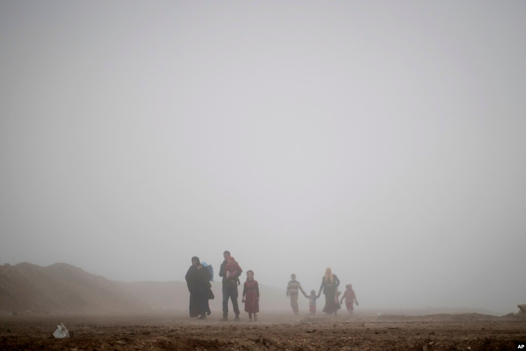 Displaced people walk through heavy fog during fighting between Iraqi security forces and Islamic State militants in west Mosul, Iraq.
