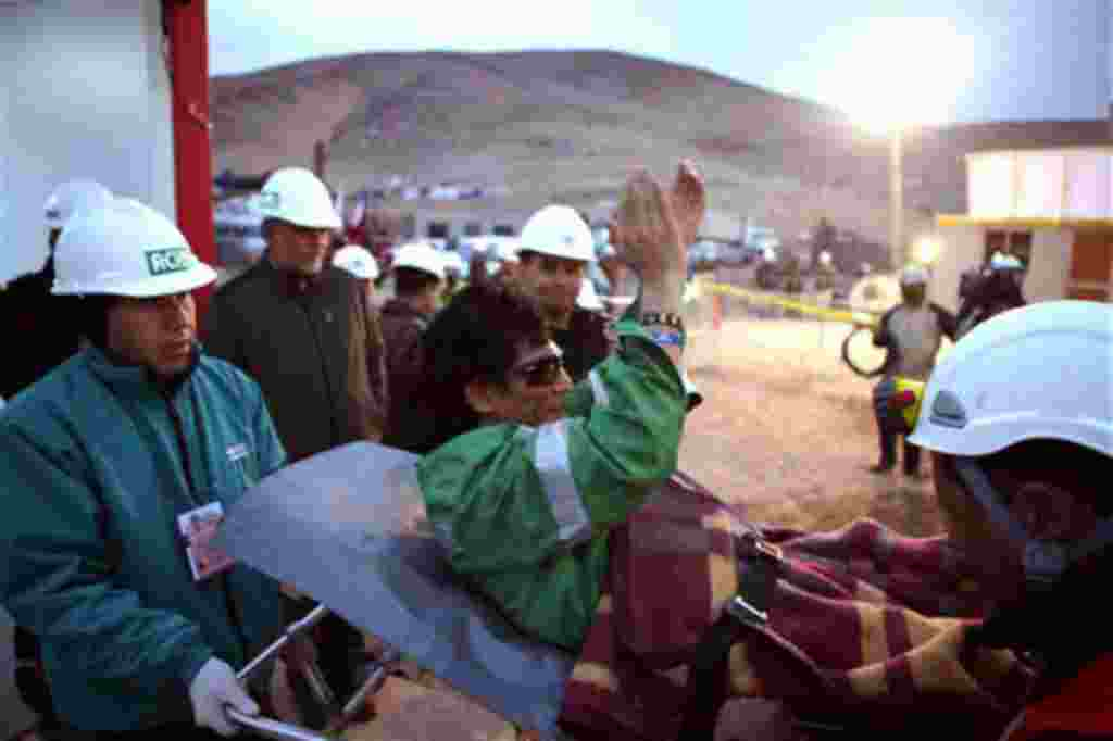 In this photo released by the Chilean government, miner Claudio Yanez applauds as he is carried away in a stretcher after being rescued from the collapsed San Jose gold and copper mine where he had been trapped with 32 other miners for over two months nea