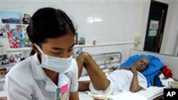 A nurse, wearing protective mask an gloves reads to a HIV/AIDS patient at the Phra Baht Nam Phu AIDS hospice near Lopburi, Thailand (File)