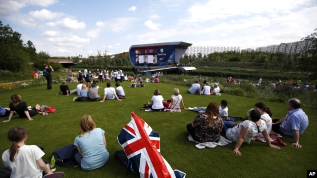 Spectators watch a live broadcast of an event at the Olympic Park during the 2012 Olympics in London, July 28, 2012.