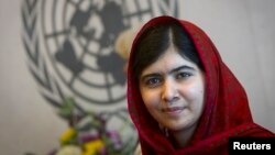 Pakistani activist Malala Yousafzai poses for pictures during a photo opportunity at the United Nations in New York, Aug. 18, 2014.