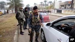 عراق کے دارالحکومت بغداد کی ایک شاہراہ پر سکیورٹی اہلکار گاڑیوں کی تلاشی لے رہے ہیں