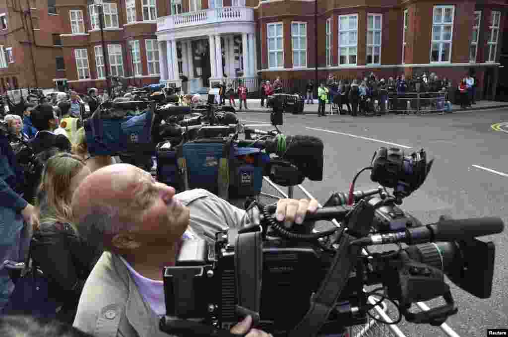 Members of the media wait outside the Ecuadorian embassy during a news conference for WikiLeaks founder Julian Assange in central London, Aug. 18, 2014.