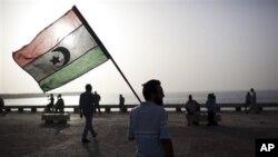 ຊາຍຄົນນຶ່ງຖືທຸງຊາດ ໃນສະໄໝກ່ອນທ່ານກາດດາຟີປົກຄອງປະເທດ ທີ່ເມືອງ Benghazi ຂອງລີເບຍ. ວັນທີ 7 ມິຖຸນາ 2011