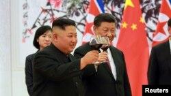 Ông Kim Jong Un và ông Tập Cận Bình chúc mừng nhau ở Bắc Kinh, Trung Quốc, ngày 20/6/2018.