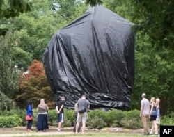 FILE - Residents and visitors look over the covered statue of Confederate General Robert E. Lee in Emancipation park in Charlottesville, Va., Aug. 23, 2017.