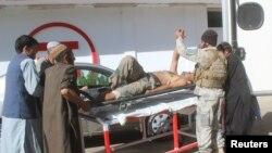 아프가니스탄 헬만드주의 압둘 자바르 카흐라만 의원 사무실에서 폭탄 공격이 있은 후 보안대원들이 부상한 경찰을 실어나르고 있다.