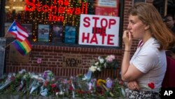 A woman cries and holds flowers in front of a makeshift memorial to remember the victims of a mass shooting in Orlando, Fla., in New York, Sunday, June 12, 2016