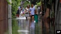 Cư dân lội qua một khu vực ngập lụt ở Bangkok. Các nhà khoa học nói rằng mực nước biển đang tăng lên và thủ đô Thái Lan có thể chìm vĩnh viễn dưới làn nước trong vài thập niên nữa.