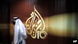 FILE - A Qatari employee of Al Jazeera Arabic language TV news channel passes by the logo of Al Jazeera in Doha, Qatar.
