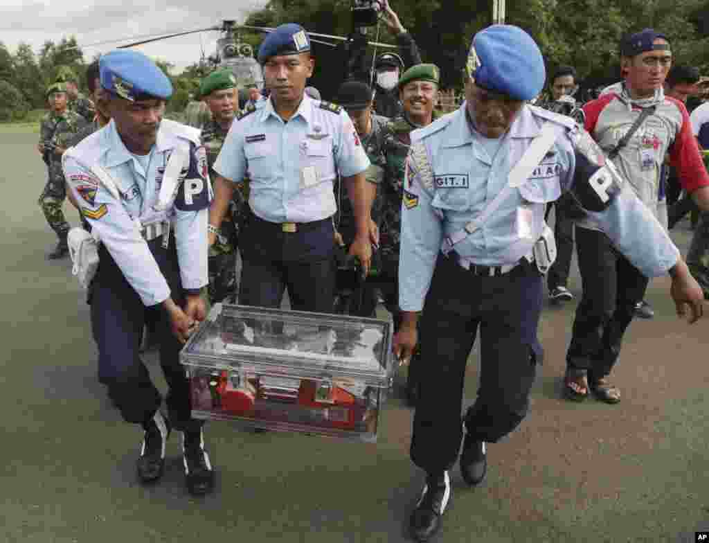 Nhân viên thuộc lực lượng không quân Indonesia xách thiết bị ghi dữ liệu chuyến bay 8501 xấu số của hãng AirAsia bị rơi ở Biển Java, tại sân bay ở Pangkalan Bun.