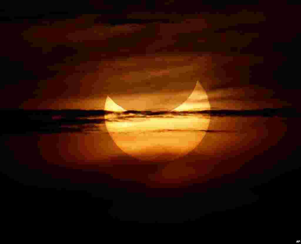Un eclipse anular solar es parcialmente visible en la salida del sol desde el municipio costero de Gumaca, al sureste de Manila, en Filipinas.
