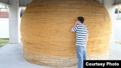 A tourist looks at the World's Largest Ball of Twine. (Credit: RoadsideAmerica.com)