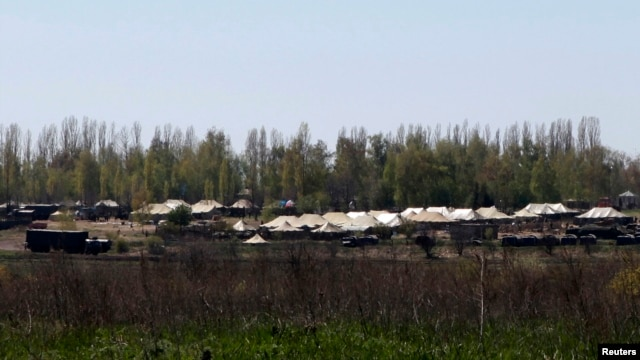 FILE - Russian military vehicles and army tents are seen in a field outside the village of Severny in Belgorod region near the Russian-Ukrainian border, April 25, 2014.