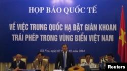 អ្នកនាំពាក្យរបស់វៀតណាម លោក Le Hai Binh (រូបកណ្តាល) ថ្លែងនៅក្នុងសន្និសីទកាសែតមួយស្តីពីការដាក់ពង្រាយម៉ាស៊ីនបូមប្រេងពីផ្នែកនៃសមុទ្រចិនខាងត្បូងដែលមានជម្លោះ នៅក្នុងក្រុងហាណូយ កាលពីថ្ងៃទី៧ ខែឧសភា ឆ្នាំ២០១៤។