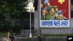 Dân chúng Bắc Triều Tiên đạp xe ngang qua một áp phích tuyên truyền trong Khu công nghiệp Kaesong.