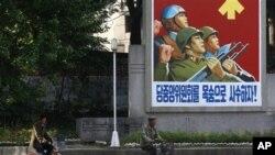 Dân Bắc Triều Tiên đạp xe ngang qua một tấm áp phích tuyên truyền tại Kaesong. 53,000 công nhân Bắc Triều Tiên được tuyển dụng ở khu này làm việc cho hơn 100 công ty Nam Triều Tiên.