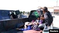Civiles, heridos por lo que activistas dicen fue un ataque del groupo Estado islámico en Kobani, esperan con sus familiares para cruzar la frontera hacia Turquía.