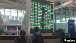 International passengers are seen near the flight information board at Ngurah Rai Bali International Airport, Kuta, Bali, Indonesia, Dec. 2, 2017.