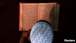 FILE - An boy reads the Quran in a madrassa religious school.