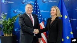 Ngoại trưởng Mỹ Mike Pompeo và bà Federica Mogherini, người đứng đầu chính sách ngoại giao EU, bắt tay trước cuộc họp ngày 15/2/2019 ở Bruxelles. (Olivier Hoslet/ Pool Photo via AP)