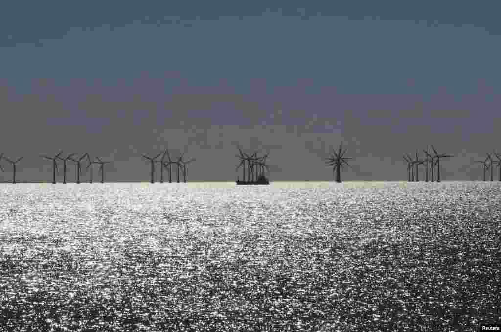 A ship passes offshore windmills on the coast near Copenhagen, Denmark, April 4, 2015.
