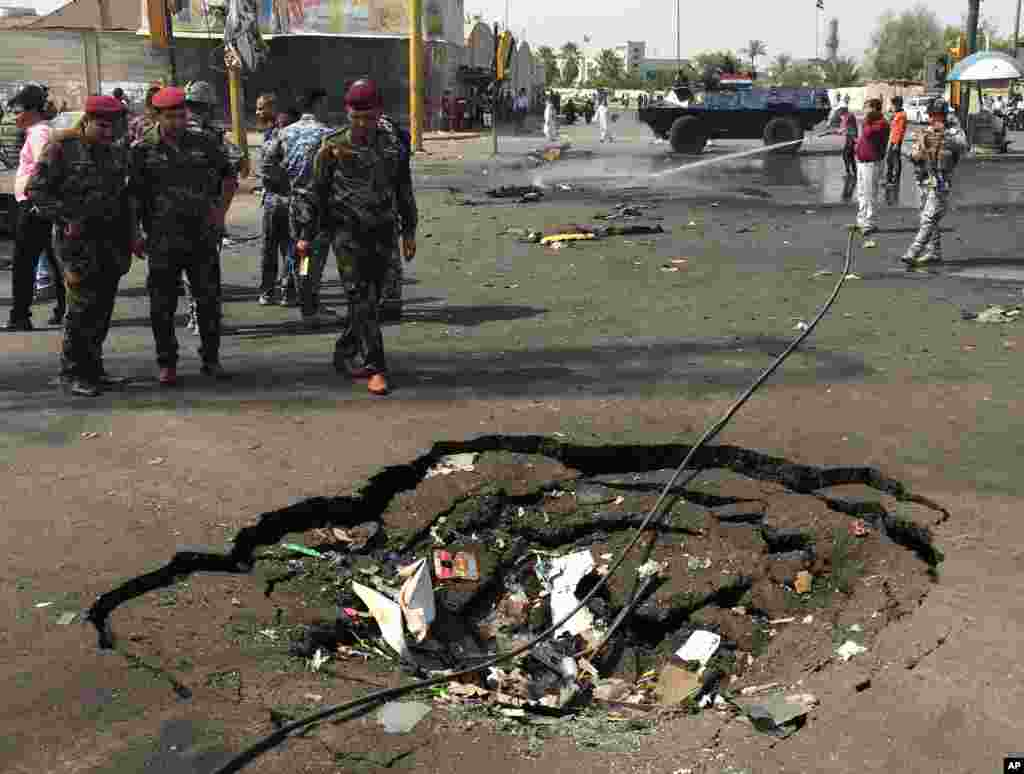 Security forces and civilians inspect a crater caused by a car bomb explosion in the commercial area of New Baghdad, Iraq, Aug. 26, 2014.