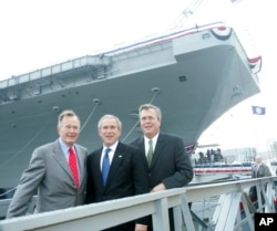 FILE - President George W. Bush, center, with former President George H.W. Bush, left, and Florida Governor Jeb Bush, right, pose in front of the aircraft carrier George H.W. Bush after participating in the christening ceremony in Newport News, Va.