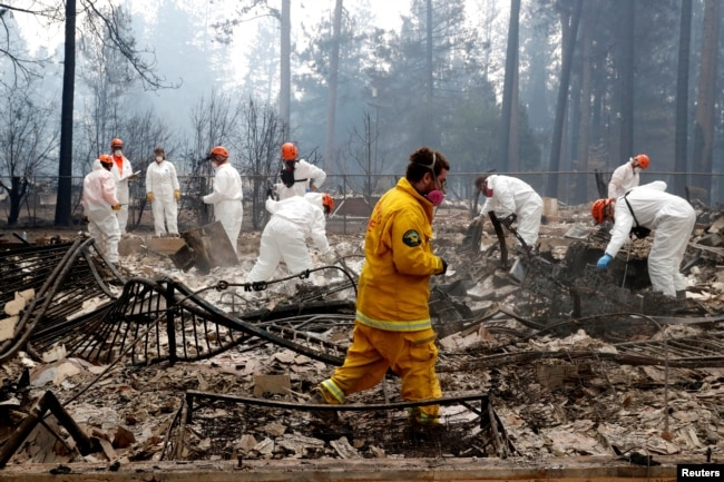 A volunteer search and rescue crew from Calaveras County comb through a home destroyed by the Camp Fire in Paradise, California, Nov. 13, 2018.