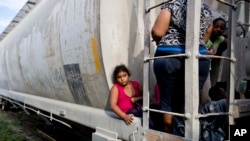 A young migrant girl waits for a freight train to depart on her way to the U.S. border, in Ixtepec, Mexico, Saturday, July 12, 2014.