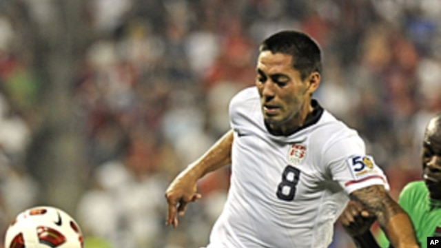 United States' Clint Dempsey (8) holds off a challenge by a Guadeloupe player during their CONCACAF Gold Cup match at Livestrong Stadium in Kansas City, Kansas June 14, 2011