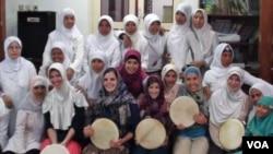 Lima mahasiswi asal Amerika (duduk di barisan depan) berfoto bersama ibu-ibu jamaah masjid di Plosokuning, Yogyakarta. Para mahasiswi AS ikut menyanyikan irama Hadrah dengan memainkan alat musik terbang.