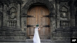 FILE - On her wedding day, a Filipino bride fixes her gown before entering a Catholic church in Manila, Philippines. (AP Photo/Aaron Favila)