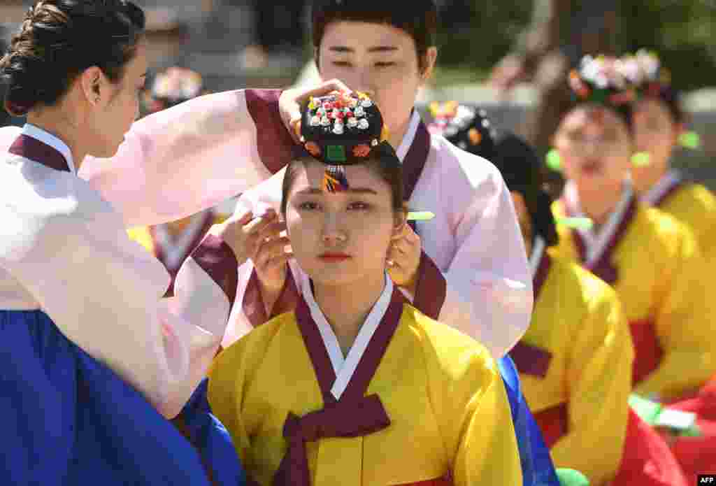 A young South Korean woman wears a traditional Korean flower cap during a traditional Coming-of-Age Day ceremony to mark adulthood at Namsan hanok village in Seoul.