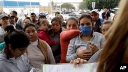 En esta foto del 23 de octubre de 2018, mujeres en Tijuana, México, observan mientras funcionarios llaman números y nombres para cruzar la frontera y solicitar asilo en Estados Unidos.