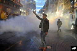 Police use teargas to disperse people protesting the killing of Tahir Elci, a prominent lawyer and human rights defender, who faced a prison term on charges of supporting Kurdish rebels, in Istanbul, Turkey, Nov. 28, 2015.