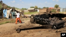 FILE - A man walks past the remains of a tank destroyed during fighting between government and rebel forces on July 10, 2016, in the Jebel area of the capital Juba, South Sudan, July 16, 2016.