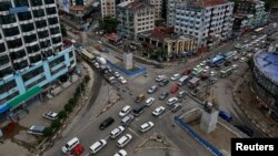 A line of vehicles drive through Shwegontai junction, one of the busiest junctions in the city, in Rangoon, July 3, 2013.