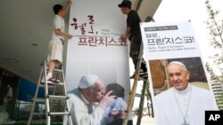 """Workers set up a poster of Pope Francis's photo exhibition """"Hello, Pope Francis!"""" at the Sejong Culture Center in Seoul, South Korea, Tuesday, Aug. 5, 2014. (AP Photo/Ahn Young-joon)"""