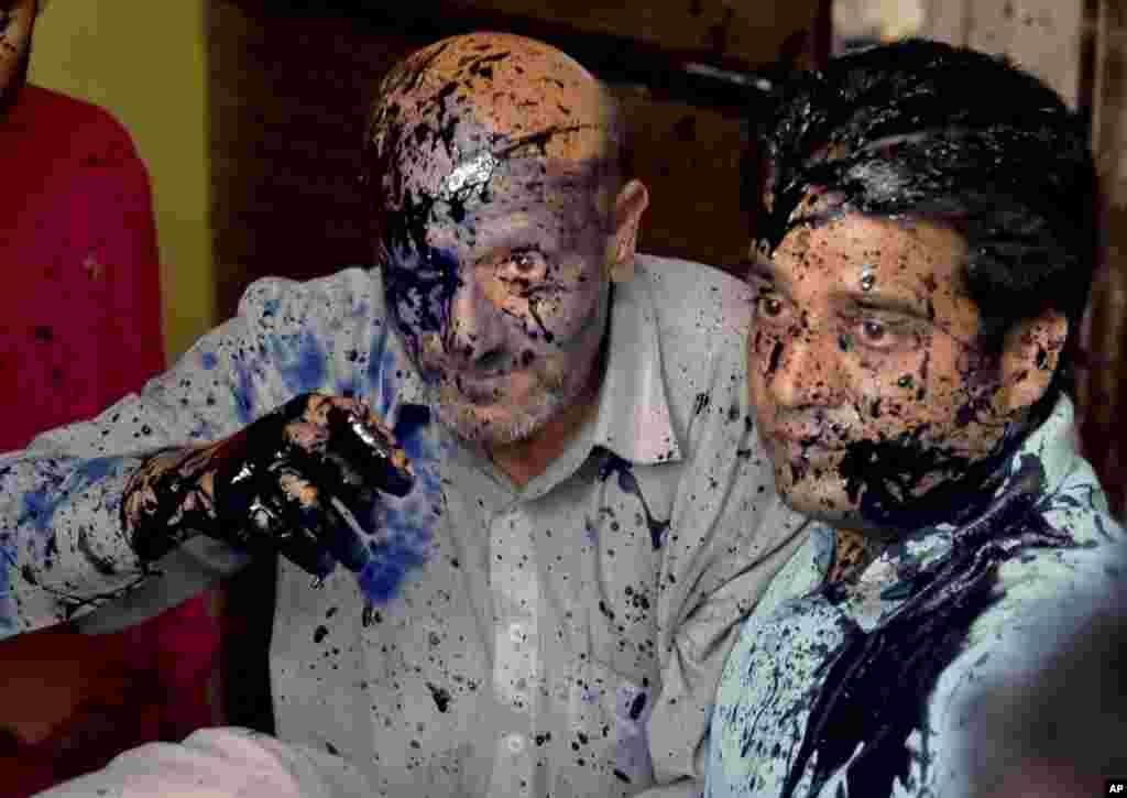 Jammu and Kashmir lawmaker Abdul Rashid Sheikh, left, reacts after suspected activists of a right-wing organization threw ink on his face at a press conference in New Delhi, India. According to local reports Rashid had been protesting against the death of a Muslim teenager attacked by a Hindu mob over rumors of cows being slaughtered.