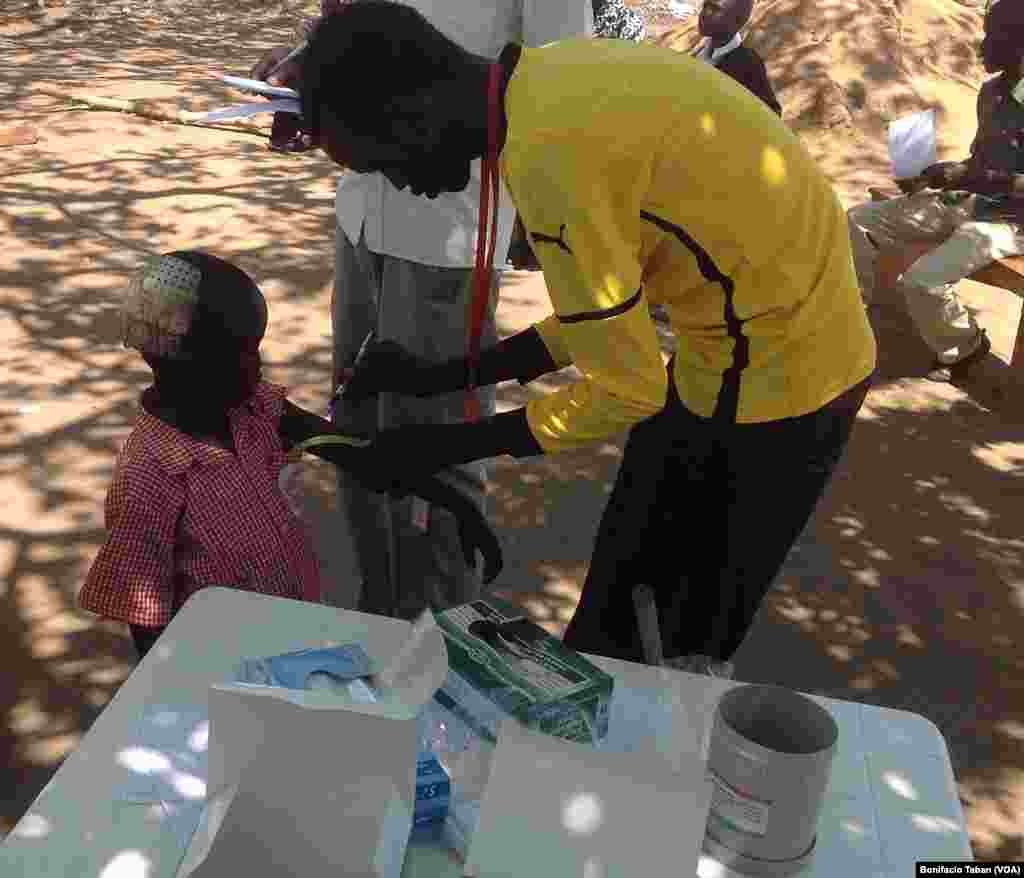 An MSF staffer tests a child's nutrition levels at a refugee resettlement camp in Uganda on March 19, 2014.