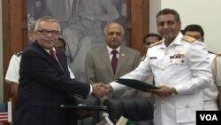 31일 나토 보급로 개방에 대해 합의 후 악수하는 파키스탄 해군 소장 파루크 아흐마드(오른쪽)와 미국 특사.