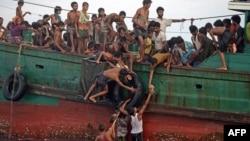 14일 로힝야 난민들이 태국 군 헬리콥터에서 투하되는 구호 식량을 건지고 있다.
