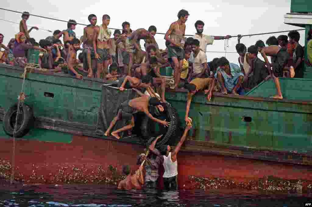 Rohingya migrants pass food supplies dropped by a Thai army helicopter to others aboard a boat drifting in Thai waters off the southern island of Koh Lipe in the Andaman sea. A boat crammed with Rohingya migrants - including many young children - was found drifting in Thai waters.