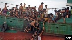 Rohingya migrants pass food supplies dropped by a Thai army helicopter to others aboard a boat drifting in Thai waters off the southern island of Koh Lipe in the Andaman sea on May 14, 2015.