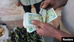 FILE - A vendor counts Syrian currency notes in Damascus, November 13, 2012.