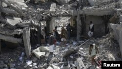 Houthi militants gather on the rubble of the offices of the education ministry's workers union, destroyed by Saudi-led air strikes, in Yemen's northwestern city of Amran, Aug. 19, 2015.