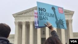 2018年4月25日,华盛顿的美国最高法院外,一名示威者举着反对旅行禁令的标语。